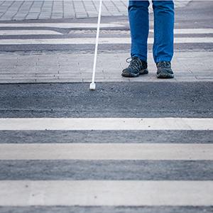 Illustrationsbild på en person med en vit käpp som stor vid en skyddsväg.