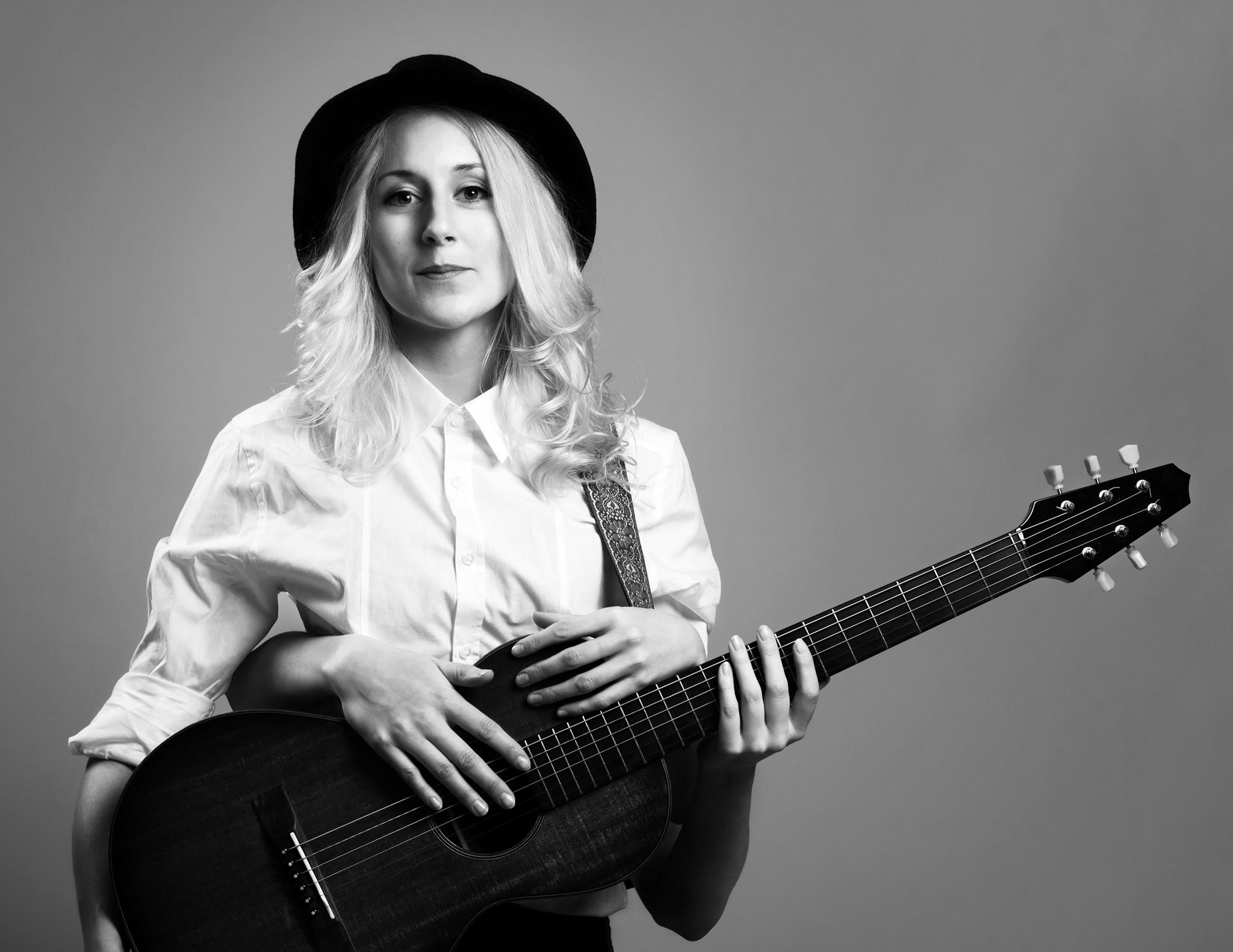 Svartvit bild på Frida Andersson med sin gitarr. Foto: Christoffer Relander