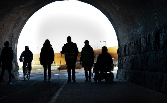 Fyra personer som står bredvid varandra varav en sitter i en rullstol och en bär en vit käpp.