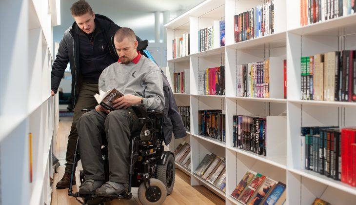 Illustrationsbild på två vänner varav den andra sitter i en rullstol i ett biliotek.