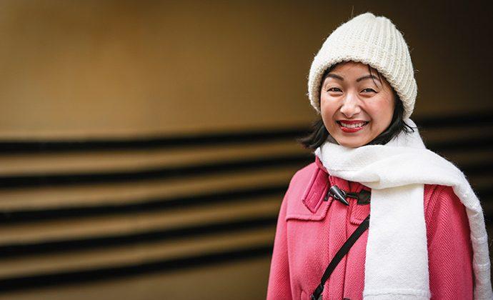 Hisayo Katsui, en japansk kvinna med ljusröd rock och vit scarf och mössa ler brett mot kameran..