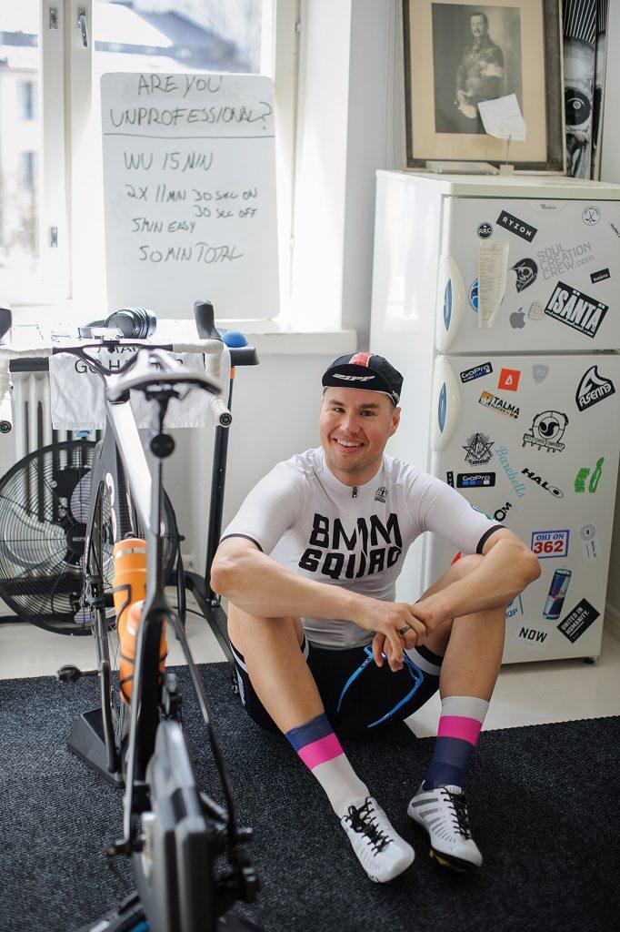 Robson sitter på golvet bredvid sin cykel i cyklingsutrustning.