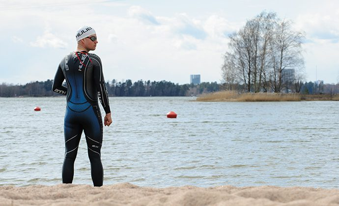 Robson Lindberg, världens bästa hjärnskadepatientpå heltid, står på en simstrand i våtdräkt.