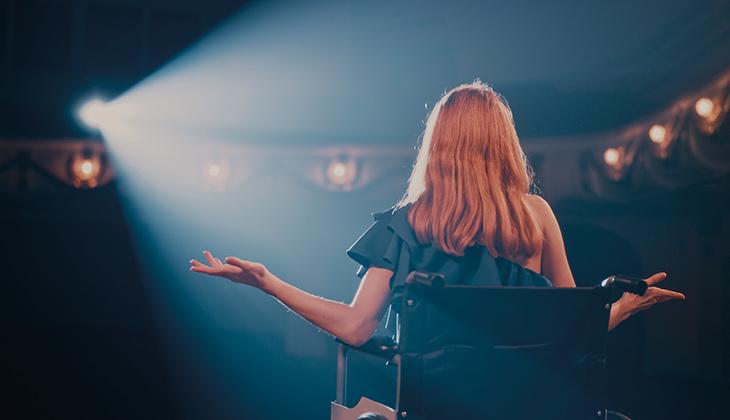 Illustrationsbild på kvinna som sitter i en rullstol på en teaterscen.