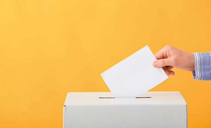 Illustrationsbild på en person som sätter en röstsedel i en valurna.