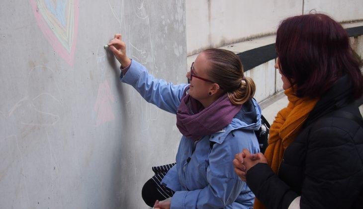 Illustrationsbild: Två kvinnor som ritar på en vägg med gatukritor.
